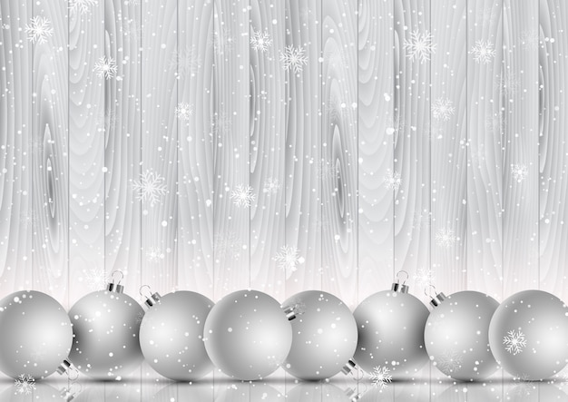 Christmas baubles on a decorative snowflake and wooden background