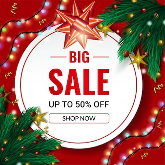 Christmas big sale banner up to 50% off sale with spruce tree branches and garland lights on red