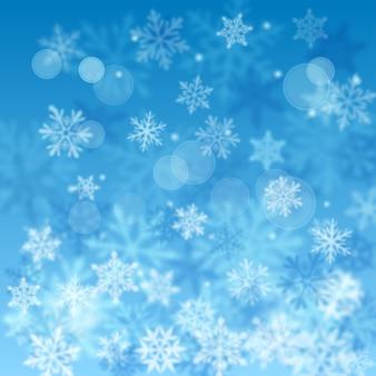 보케 효과가 있는 밝은 파란색의 복잡한 디포커스 크고 작은 눈송이의 크리스마스 흐릿한 배경