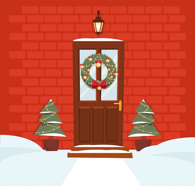 Christmas brown door with wreath, snow and firs on red brick wall. forged lantern above the door shines.