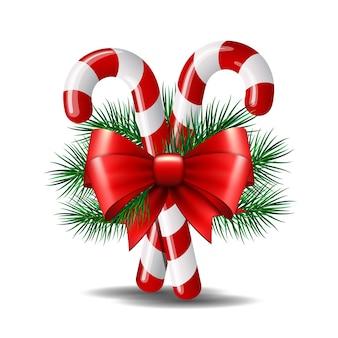 白地に赤の弓とクリスマスツリーブランチのクリスマスキャンデー杖。図。