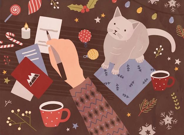 손으로 펜을 잡고 휴일 엽서, 귀여운 고양이, 커피 한 잔, 과자, 축제 계절 장식에 글을 쓰는 크리스마스 카드 템플릿. 평면 만화 스타일의 다채로운 벡터 일러스트 레이 션.