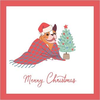 クリスマスツリーの近くの毛布に座っているブルドッグとクリスマスカード