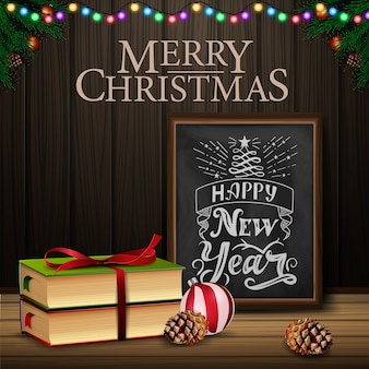 Christmas card with chalkboard and christmas book on wood background