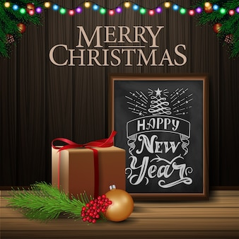 Christmas card with chalkboard and gifts on wood background
