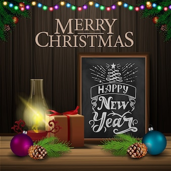 Christmas card with chalkboard and old lantern on wood background