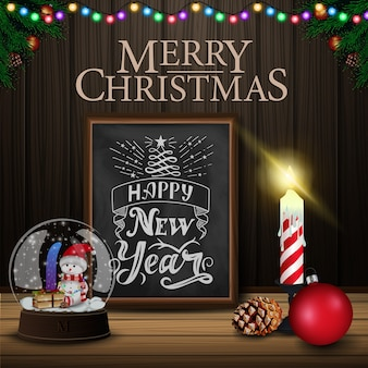 Christmas card with chalkboard, snow globe and candle on wood background
