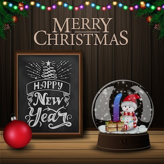 Christmas card with chalkboard and snow globe on wood background