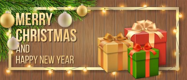 ギフトボックス、クリスマスツリーの枝と木製の背景に花輪とクリスマスカード。