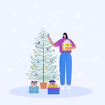 クリスマスのキャラクターと装飾。若い美しい女性がクリスマスツリーを飾ります。クリスマスツリーと雪片の下の贈り物