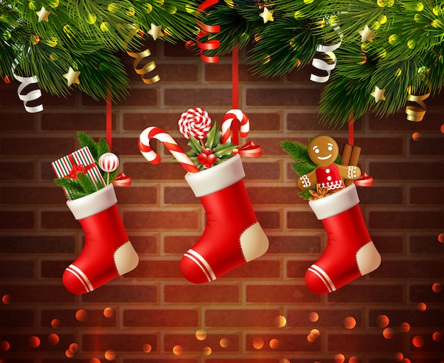 Christmas composition with festive socks filled with gifts and fir needle with brick wall