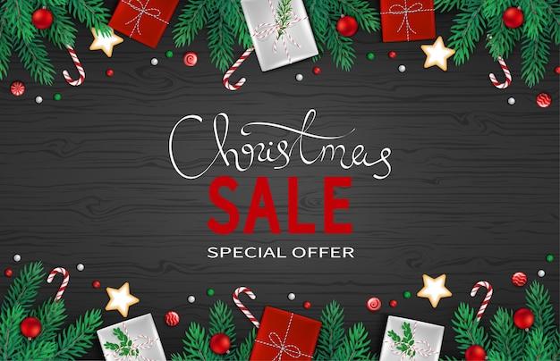 Рождественские скидки распродажа баннер с еловыми ветками, подарочными коробками, шарами большая сезонная распродажа. специальное предложение
