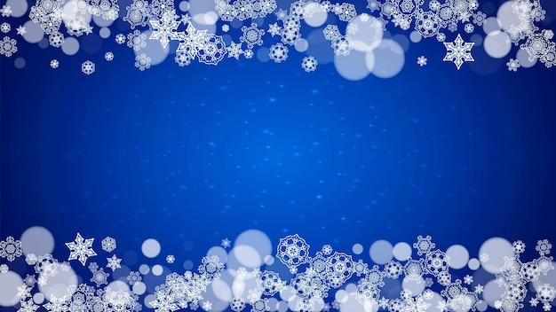 반짝임과 파란색 배경에 떨어지는 눈 크리스마스 프레임. 배너, 선물 카드, 파티 초대장 및 특별 비즈니스 제안을 위한 흰색 서리가 내린 눈송이가 있는 수평 크리스마스 프레임.