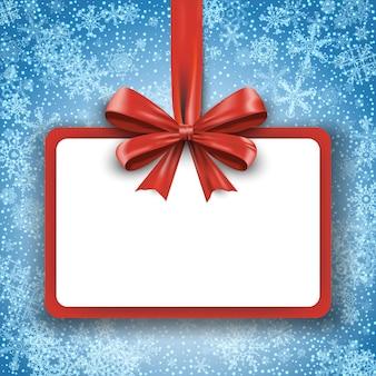 Рождественская подарочная карта с красной лентой и атласным бантом на фоне снежинок