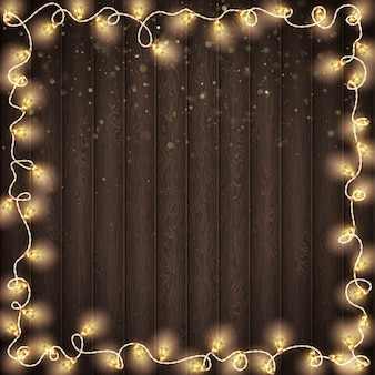 クリスマス輝く暖かいライト。ダークブラウンの木製の背景。年末年始のグリーティングカードのコンセプトです。そしてまた含まれています