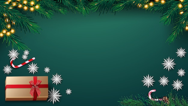 Christmas green background with garland, christmas tree, present, paper snowflakes and candy can, top view