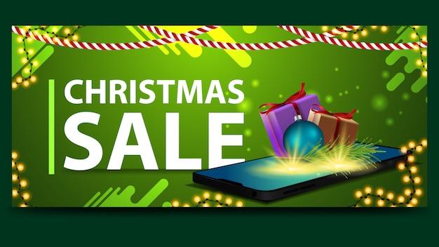 Новогодний зеленый дисконтный баннер со смартфоном, с экрана которого появляются подарки