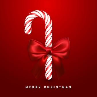 赤い弓とリボンでリアルなキャンディケインとクリスマスの挨拶