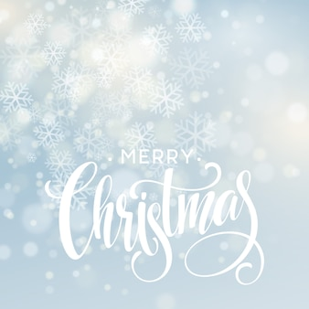 Christmas handwritten lettering text on blurred background with lights.