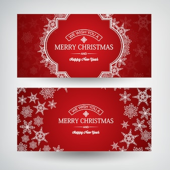 Christmas and happy new year horizontal banners with greeting inscriptions and beautiful snowflakes on red