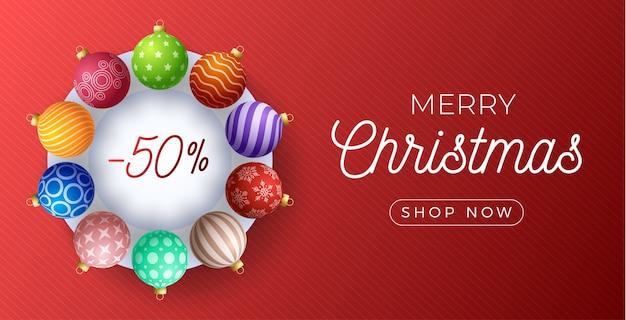 Рождественские горизонтальные продажи промо-баннер. праздничная иллюстрация с реалистичными декоративными красочными рождественскими шарами на красном фоне.