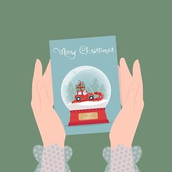 Рождественские иллюстрации женские руки держат поздравительную открытку со снежным стеклянным шаром