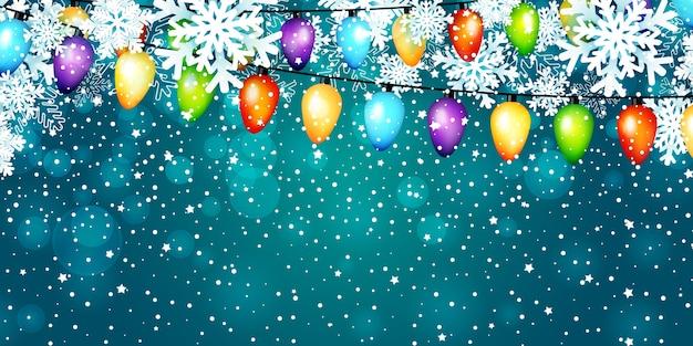 Рождественские гирлянды лампочек и бумажные snowflakws на синем фоне.