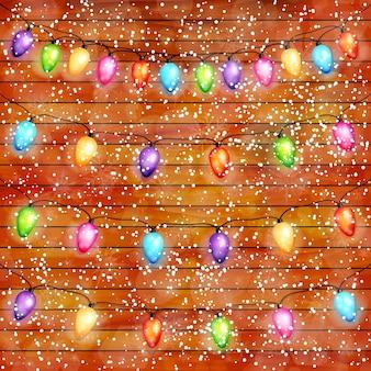 Рождественские гирлянды из лампочек на деревянных фоне