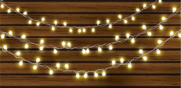 어두운 나무 배경에 고립 된 크리스마스 조명입니다. 광선 갈 랜드 전구 전선.