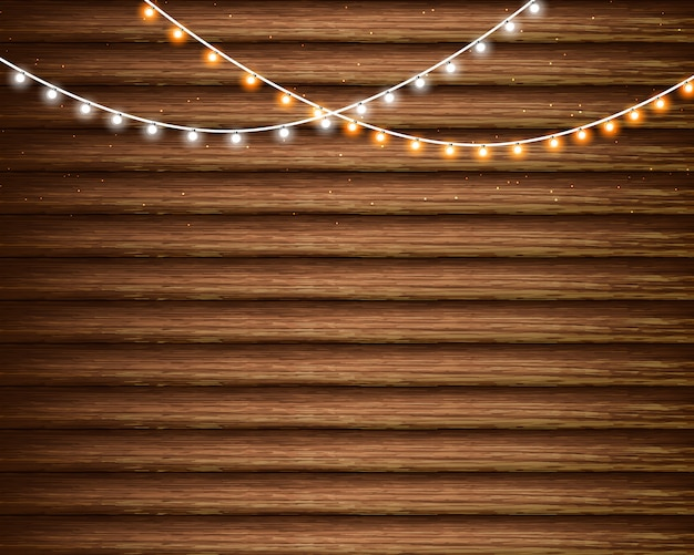 Christmas lights on the wooden background