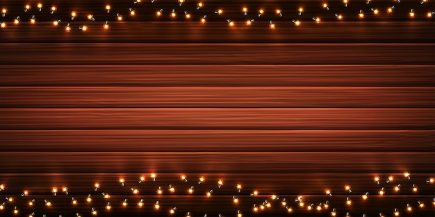 Christmas lights. xmas glowing garlands of led light bulbs on wooden background