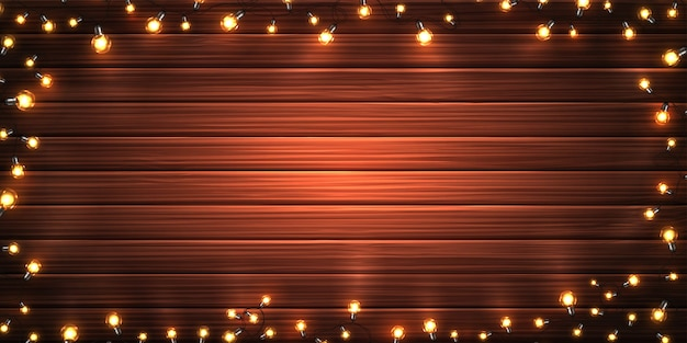 Christmas lights. xmas glowing garlands of led light bulbs on wooden texture background
