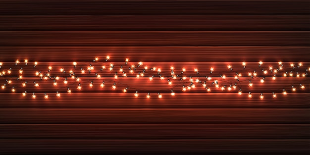 Christmas lights. xmas glowing garlands of led light bulbs on wooden texture.