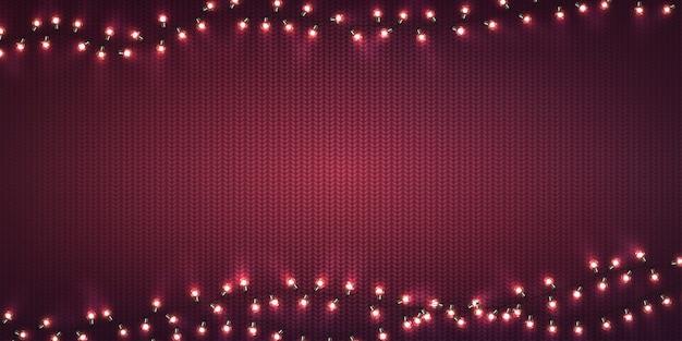 Рождественские огни. рождественские светящиеся гирлянды из светодиодных лампочек на фиолетовой вязаной текстуре.