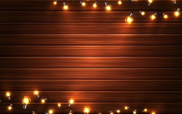 Рождественские огни. xmas светящиеся гирлянды светодиодные лампочки на фоне деревянной текстуры. праздничные украшения
