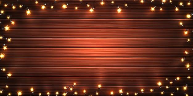 Рождественские огни. рождественские светящиеся гирлянды из светодиодных лампочек на деревянном фоне текстуры