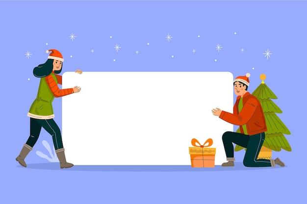 空白のバナーを保持しているクリスマスの男性と女性