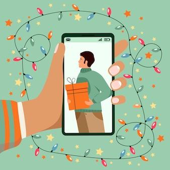 Рождество новая нормальная концепция с рукой, держащей телефон во время видеозвонка. рождественская онлайн вечеринка.