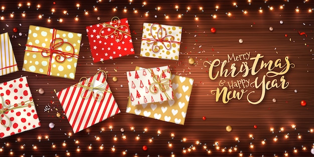 Christmas and new year background with gift boxes, xmas garlands of lights, baubles and glitter confetti on wooden texture.