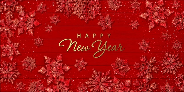Christmas and new year banner with sparkling glass snowflakes on red wooden background