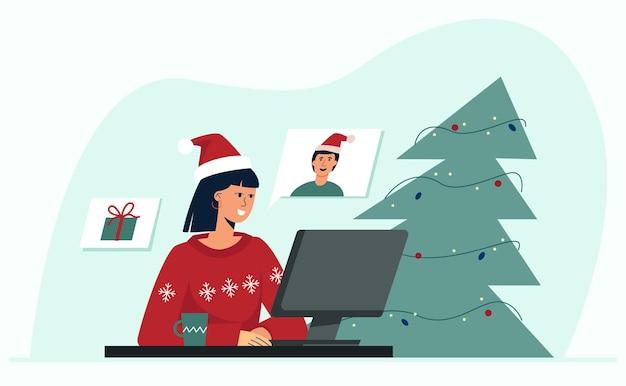 크리스마스 온라인 젊은 예쁜 여자가 화상 회의를 통해 친구와 의사 소통합니다.
