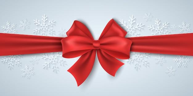 Рождественская красная лента с бантом на фоне бумажных снежинок. роскошная, шелковая лента. концепция с новым годом. графика для зимней распродажи. элемент вектора синхронизации для праздника. eps 10