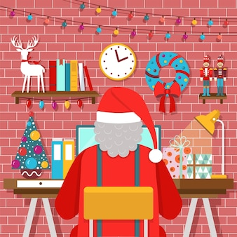Christmas room interior with santa claus at workplace working on laptop
