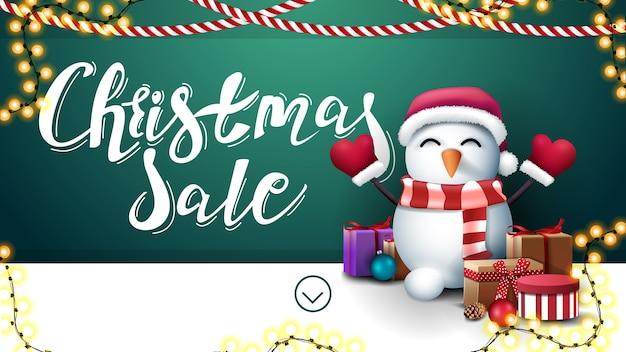 크리스마스 판매, garlands와 벽 근처 선물 산타 클로스 모자 눈사람 녹색과 흰색 할인 배너