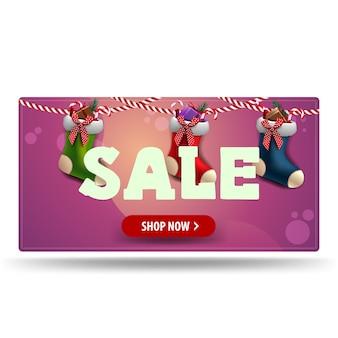 Рождественская распродажа, розовый баннер со скидкой с красной кнопкой и рождественские чулки