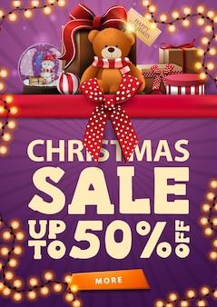 Рождественская распродажа, фиолетовый вертикальный баннер со скидкой с красной горизонтальной лентой с бантом, гирляндой и подарками с мишкой тедди