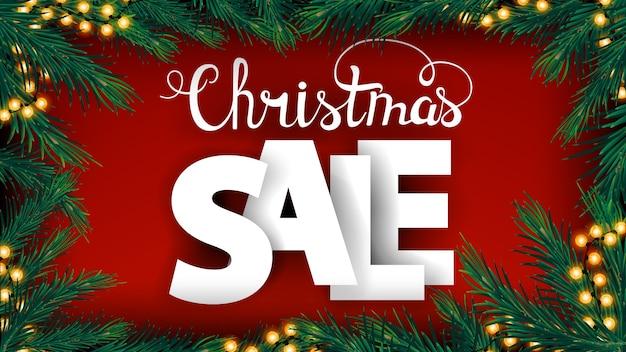 クリスマスセール、大きなボリュームの文字とクリスマスツリーの枝と花輪のフレームと赤い割引バナー