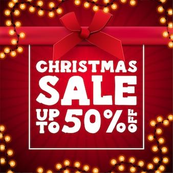クリスマスセール、花輪のフレームが付いたプレゼントボックスの形の赤い正方形の割引バナー、大きな白いオファーとリボン付きの大きな赤い弓