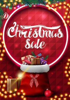 Рождественская распродажа, красный вертикальный баннер с гирляндой, ветки елки, неоновый круг, красивые надписи и сумка санта-клауса с подарками