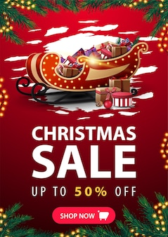Christmas sale, up to 50% off, vertical red discount banner with abstract reggad shape, garland frame, frame made of christmas tree branches, button and santa claus sleigh with pile of presents